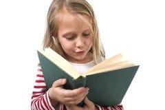 Молодые сладостные маленькие 6 или 7 лет при девушка светлых волос читая книгу смотря любознательный и fascinated стоковое изображение rf