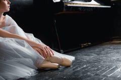 Молодые танцы балерины, крупный план на ногах и ботинки, усаживание в shooses pointe Стоковые Изображения RF
