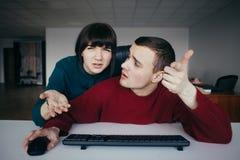 Молодые товарищ и женщина смутили смотреть монитор компьютера Битник в современном офисе Стоковые Изображения