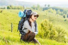 Молодые укладывая рюкзак остатки женщины на холме Стоковая Фотография RF
