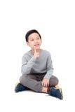 Молодые усаживание и улыбки мальчика над белизной Стоковое Изображение