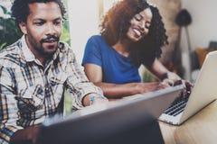 Молодые усмехаясь Афро-американские пары работая совместно дома Молодой чернокожий человек и его подруга используя компьтер-книжк Стоковое Фото