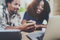 Молодые усмехаясь Афро-американские пары работая совместно дома Молодой чернокожий человек и его подруга используя компьтер-книжк Стоковое Изображение