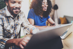 Молодые усмехаясь Афро-американские пары работая совместно дома Молодой чернокожий человек и его подруга используя компьтер-книжк Стоковые Изображения RF
