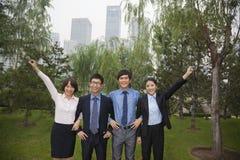 Молодые усмехаясь бизнесмены в парке, портрет в ряд стоковое фото rf