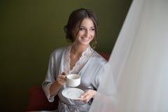 Молодые усмехаясь гонорары невесты девушки Стоковая Фотография