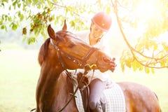 Молодые усмехаясь губы женщины всадника касающие лошади Стоковая Фотография