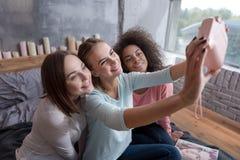 Молодые усмехаясь девушки принимая selfie в спальне дома Стоковая Фотография RF