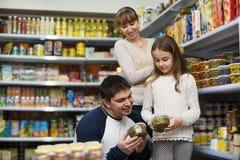 Молодые усмехаясь залуживанные родители с приобретением маленькой девочки Стоковое фото RF