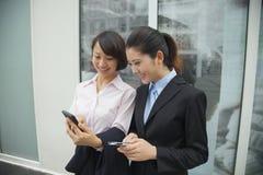 Молодые усмехаясь коммерсантки смотря их сотовые телефоны вне офисного здания Стоковое Изображение
