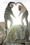 Молодые усмехаясь пары делая сердце формируют с их оружиями снаружи Стоковое Фото