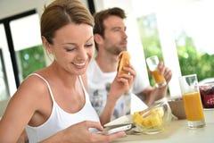 Молодые усмехаясь пары наслаждаясь завтраком Стоковая Фотография