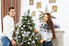 Молодые усмехаясь пары рождественской елкой Стоковое фото RF