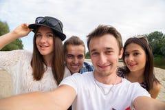 Молодые усмехаясь друзья принимая Selfie на песчаном пляже Стоковые Фотографии RF