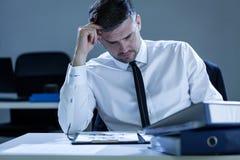 Молодые, утомленные примечания чтения бизнесмена Стоковая Фотография