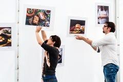 Молодые фотографы подготавливая выставку фото Стоковое фото RF