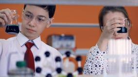 Молодые химикаты темноты смешивания и встряхивания ученых сток-видео