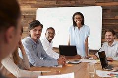 Молодые чернокожая женщина и коллеги на встрече усмехаются к камере Стоковое Изображение