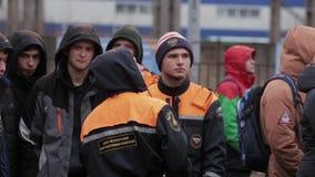 Молодые человеки в оранжевых куртках emercom остаются на улице группа смелости снаружи акции видеоматериалы