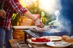 Молодые человеки жаря в духовке барбекю на гриле в сельской местности коттеджа Стоковое Изображение RF