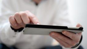 Молодые человеки используя цифровую таблетку в зеленом парке сток-видео