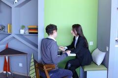 Молодые человеки и женщины связывают и делят секреты, сидя внутри внутри Стоковые Фотографии RF