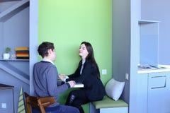 Молодые человеки и женщины связывают и делят секреты, сидя внутри внутри Стоковое Изображение RF