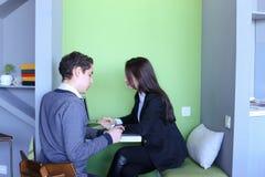 Молодые человеки и женщины связывают и делят секреты, сидя внутри внутри Стоковая Фотография