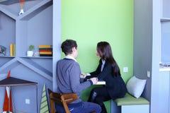 Молодые человеки и женщины связывают и делят секреты, сидя внутри внутри Стоковые Фото