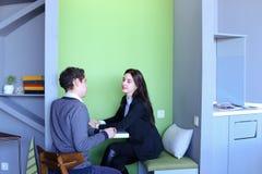 Молодые человеки и женщины связывают и делят секреты, сидя внутри внутри Стоковое фото RF