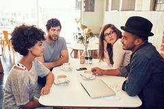Молодые человеки и женщины сидя на кафе Стоковые Фотографии RF