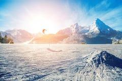 Молодые человеки, катаясь на лыжах на замороженном озере в горах, в лучах o Стоковые Изображения RF