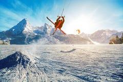 Молодые человеки, катаясь на лыжах на замороженном озере в горах, в лучах восходящего солнца, в зиме Стоковые Изображения RF