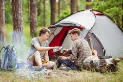 Молодые человеки нагреты в огне и кашеваре вне на летнего лагеря стоковое фото