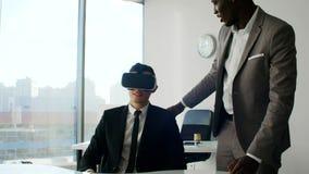 Молодые человеки нося шлемофоны виртуальной реальности в белом будущем белом офисе акции видеоматериалы