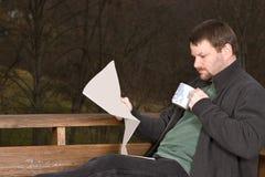 Молодой человек с кофе и газетой Стоковое Изображение