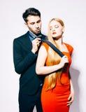 Молодые человек и женщина моды против белой стены, представляя для камеры Женщина вытягивает человека для связи крыто цвет теплый стоковое фото rf