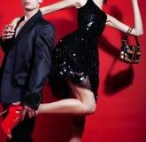 Молодые человек и женщина пар стиля моды на красной сексуальной предпосылке, роскошном веществе, концепции продажи людей образа ж Стоковое фото RF