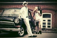Молодые человек и женщины моды рядом с винтажным автомобилем Стоковые Изображения RF
