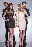 Молодые элегантные люди стоя за женщинами Стоковое фото RF