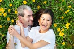 Молодые любящие пары лежа на зеленой траве с одуванчиком Стоковое Изображение