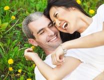 Молодые любящие пары лежа на зеленой траве с одуванчиком Стоковые Фотографии RF