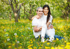 Молодые любящие пары на зеленой траве с одуванчиком Стоковая Фотография
