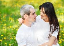 Молодые любящие пары на зеленой траве с одуванчиком Стоковые Изображения