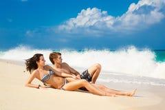 Молодые любящие пары на тропическом пляже стоковые фото