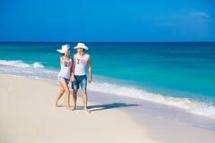 Молодые любящие пары на тропическом пляже стоковое фото