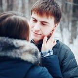 Молодые любящие пары обнимая в лесе зимы стоковые фото