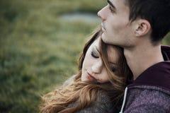 Молодые любящие пары сидя на траве стоковая фотография rf