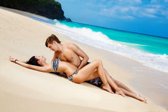 Молодые любящие счастливые пары на тропическом пляже, кладя на песок Стоковая Фотография