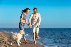 2 молодые люди бежать на пляже целуя и держа туго с собакой Стоковые Фото